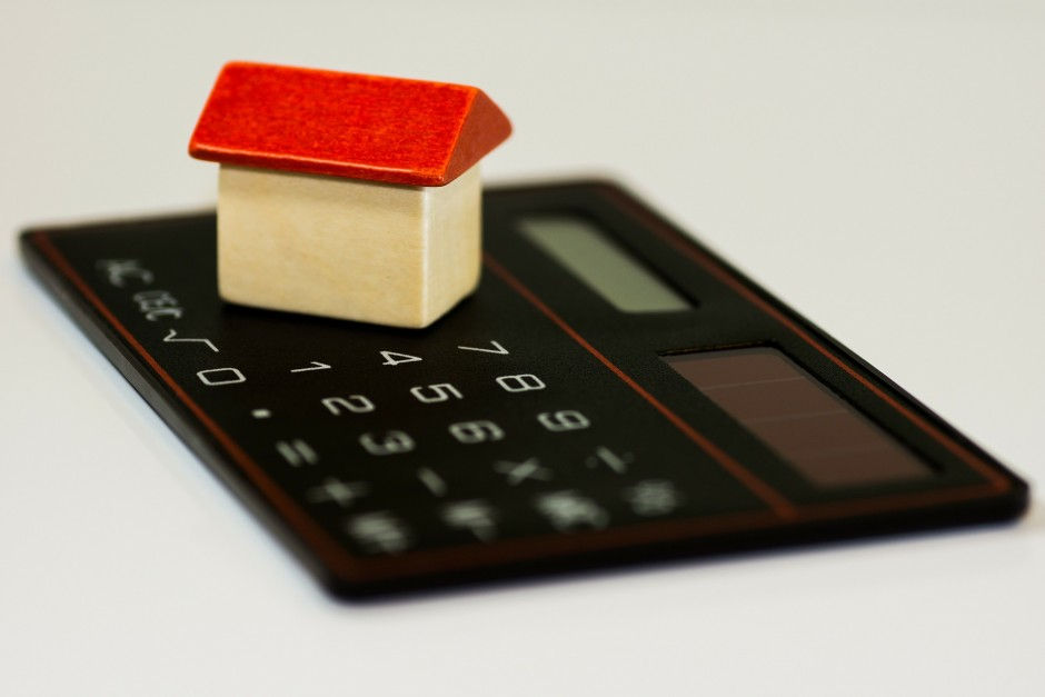 Coloured image of tiny wooden block house with natural coloured oblong block building and red triangular block roof, sitting on top of a calculator