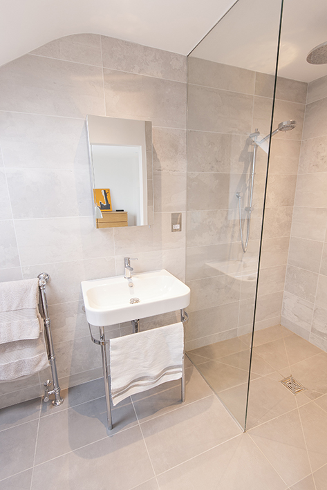 A fixed glass screen in this stylish loft conversion bathroom keeps the rest of the wet room dry.