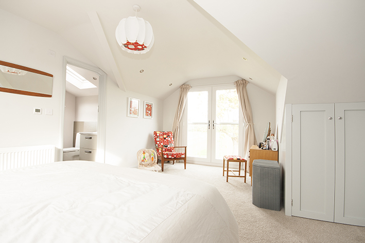 Photo of a modern loft conversion bedroom with a dormer. Double doors bring light in, and afford views. The room is decorated white with accents of red in a modern, chic print on an armchair, curtains and interior of the designer ball-style pendant light.
