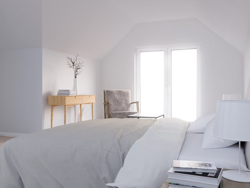 A bedroom in a dormer loft conversion. White and bright, featuring exterior double doors to make the most of light and views