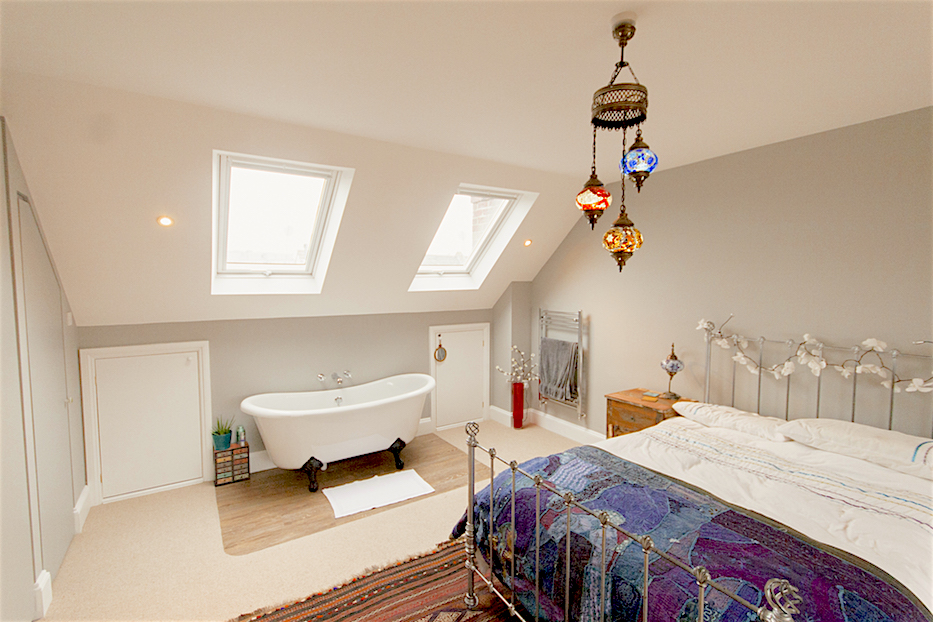 A double loft bedroom painted in warm white features Moroccan bedding, light fittings and rugs,. Under the double Velux windows to the rear is a claw footed bath situated on an area of tiled floor.