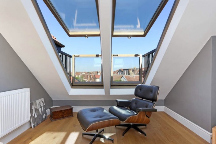 A stylish designer leather and wood Eames chair with matching foot stool waits under double, open, Velux Cabrio Balcony windows. Inside there is a medium toned wood floor and white and grey walls. Outside the sky is blue.
