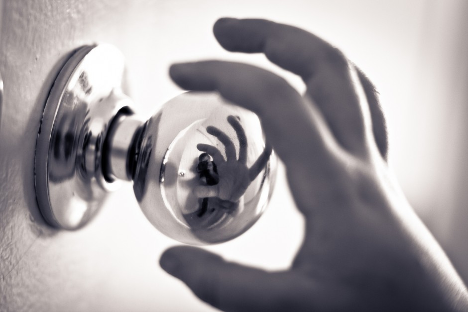 black and white photo of a child's hand reaching for a shiny door knob, the hand is reelcted in the door knob.