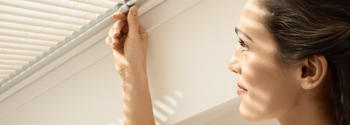 Photo close-up of a woman opening a slatted blind on a Velux roof window
