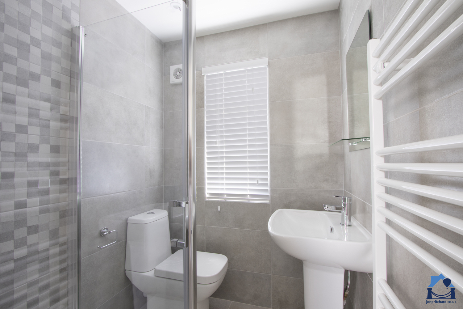 Though small, this loft conversion en-suite features a good sized shower with easy-clean glass screen, loo and free standing basin.