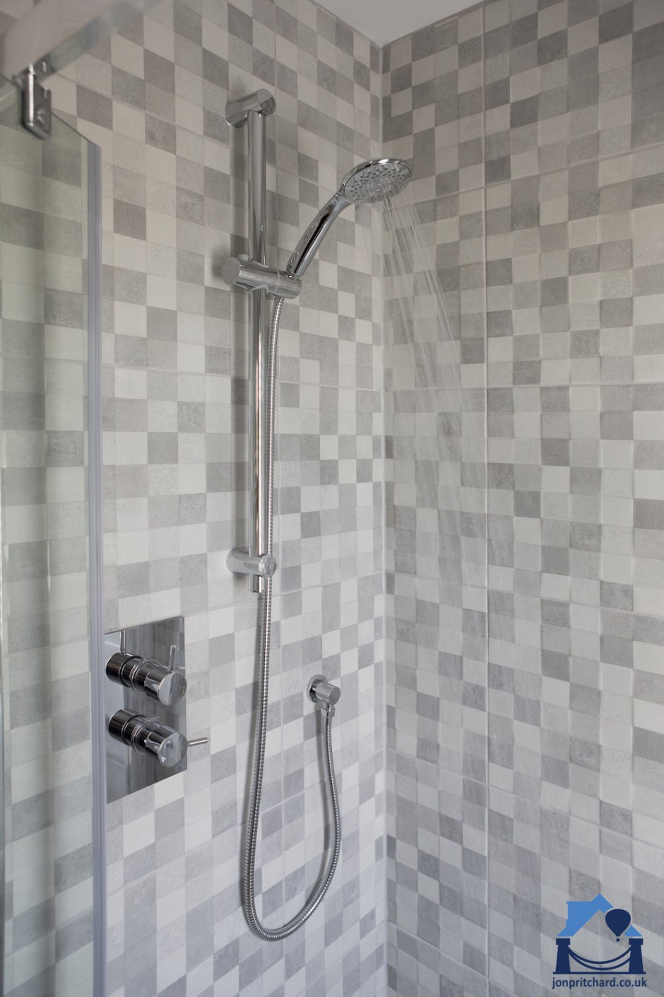 Portriat orientation photo of a modern tiled shower enclosure in attractive grey 'large' mosaic matt tiles. The water is running, shower is facing right.