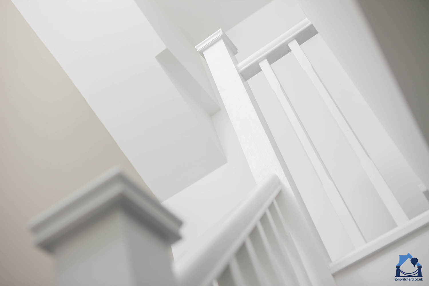 Looking up at painted white modern bannisters