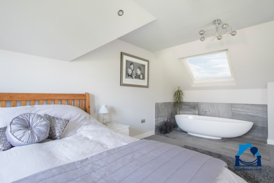 Photo of a modern, chic, loft conversion double bedroom featuring a free standing oval bath under a velux window