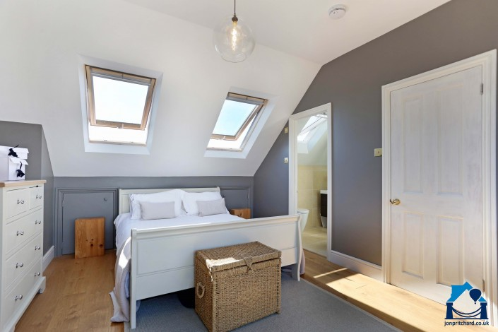 View of a double bedroom in a loft conversion, showing double bed with two Velux roof windows above. The room is decorated white for the ceilings and sloped walls, grey walls and mid tone natural wood floors.