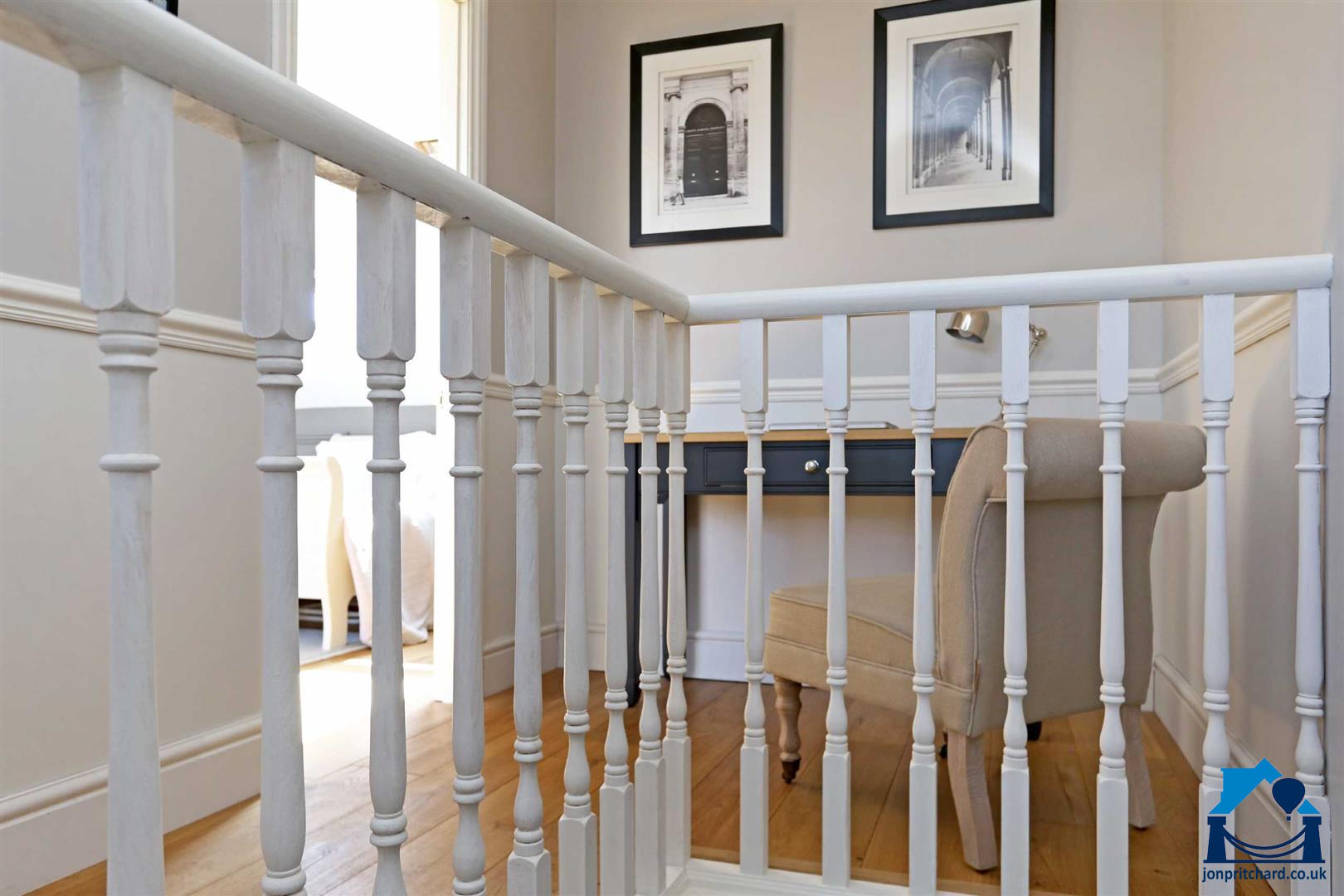 Photo showing a small landing study space in a stylish loft conversion featuring traditional staircase spindles painted white.