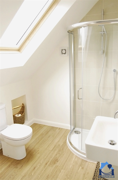Image of a loft conversion shower room with curved corner shower unit behind the white basin to the right, simple loo left, eaves storage, light wood flooring and a wood-framed Velux window in the sloping ceiling.