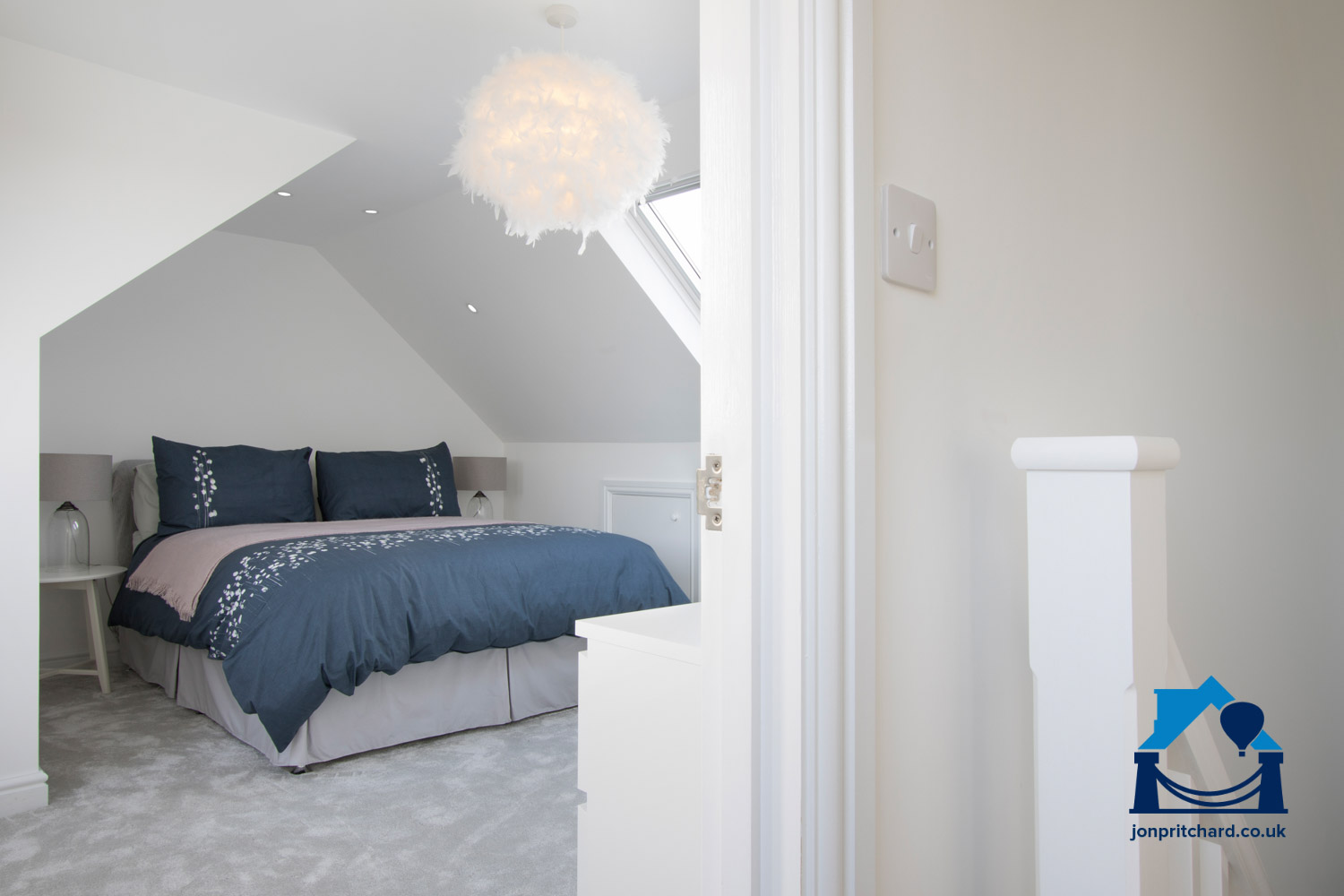 Image showing a loft conversion master bedroom, taken through the door from the landing. A bright room carpeted in light grey, with navy bedding and VELUX windows visible