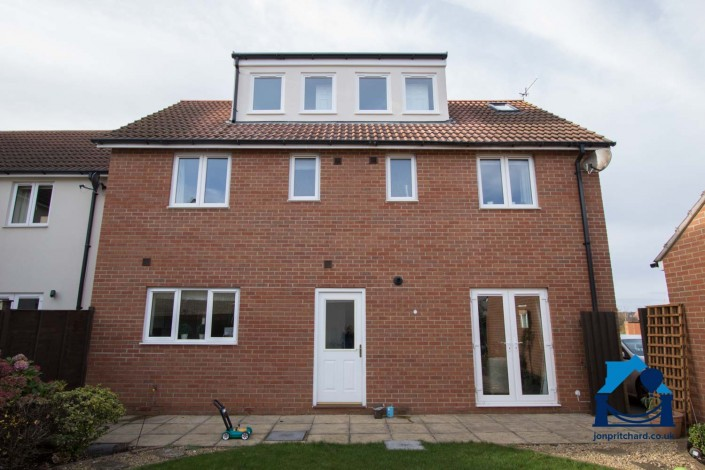Image of rear of a new build detached home, with a loft conversion that includes an attractive long flat-roofed dormer.