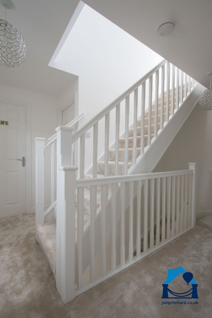 Portrait orientation photo of a generous staircase leading from a spacious first floor landing to a fully integrated loft coversion.