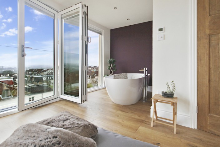 Bi-fold doors open on a glass juliet balcony showing an attractive suburban view on a clear day. A luxury bath in an l-shaped bedroom looks out over the city or the stars.