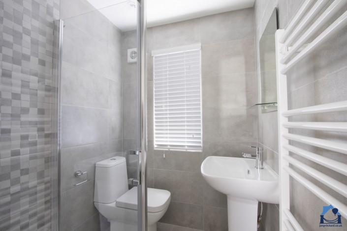 Landscape orientation photograph of a small en-suite shower room. The shower cubicle is barely visible to the left, beyond it is a modern loo and to the right a full sized pedestal basin, both in white. The oblong window in the rear wall features venetian blinds. The whol room is tiled in matt grey with some large mosaic-style tiles that blend in.