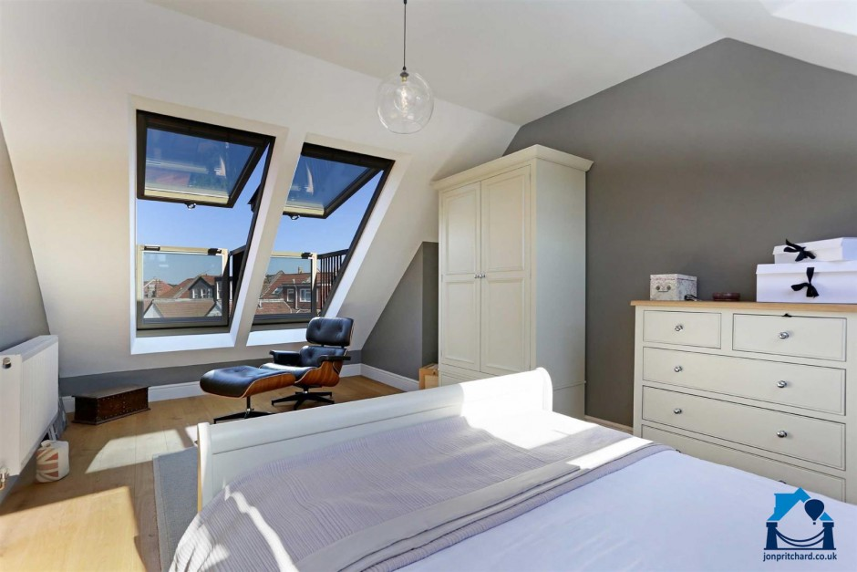 Photo of a loft conversion bedroom with stylish white wooden furniture including a tidy large double bed, wardrobe and chest of drawers. The far sloped wall features two Velux Cabrio roof windows, open in their balcony position, with blue sky and a view of red tiled rooftops. Sun streams into the room.