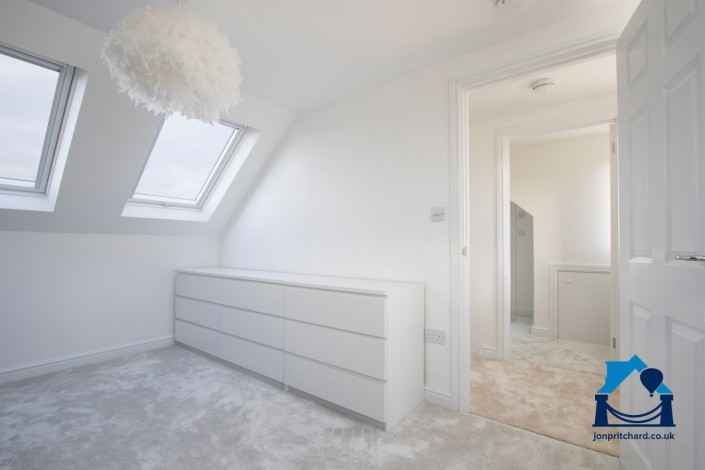 Landscape orientation photo showing the room flow of a loft conversion, from double bedroom through the door to a small landing, and dressing room/ensuite beyond