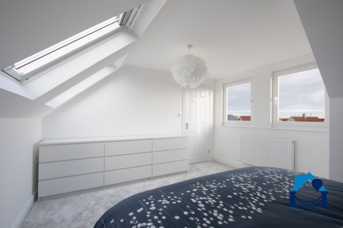 Interior image of a loft conversion bedroom, showing vertical windows in a flat roofed dormer, overlooking the neighbourhood.