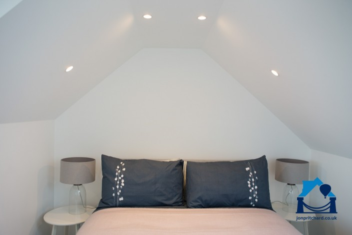 Feature of top end of double bed with pillows in dark blue, under the eaves of a loft conversion, with spotlights