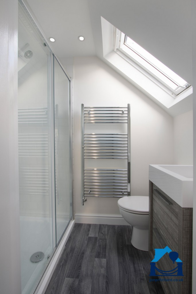 Portrait orientation image of a chic loft conversion ensuite shower room, with VELUX window.