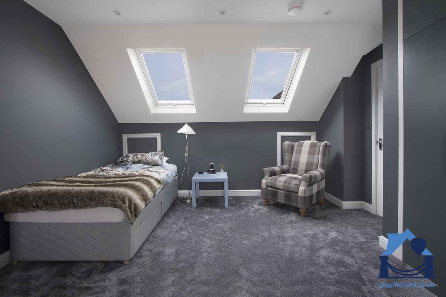 Photo showing a stylish loft conversion bedroom with single bed, armchair, fitted wardrobes and two VELUX windows