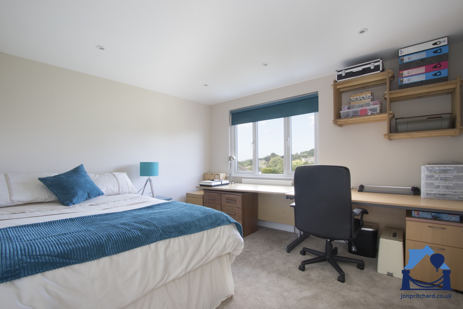 Loft bedroom with long desk and office furniture along the wall with window