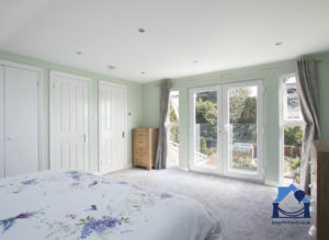 double bedroom in a Bristol loft conversion showing view across the bed to double doors with a garden view